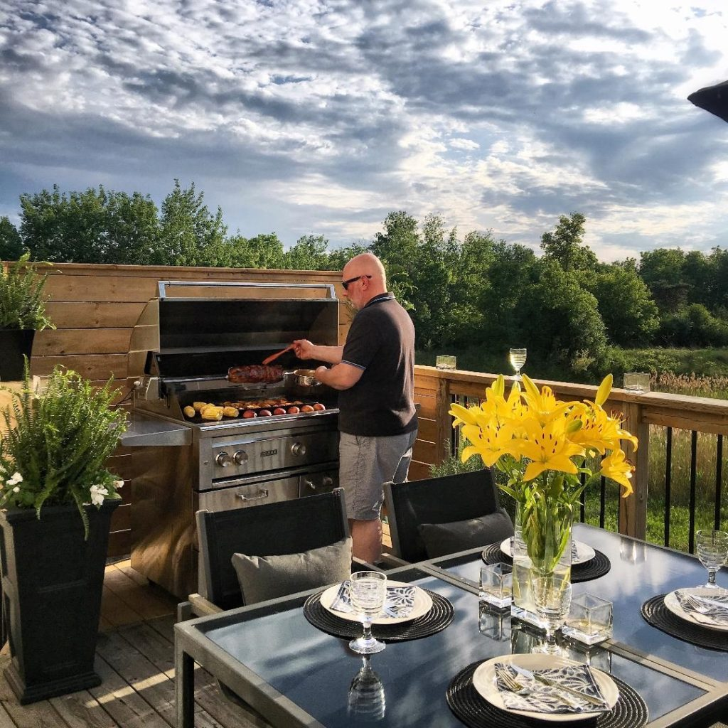 James, a Canadian food influencer,  is outside standing by his grill filled with food.
