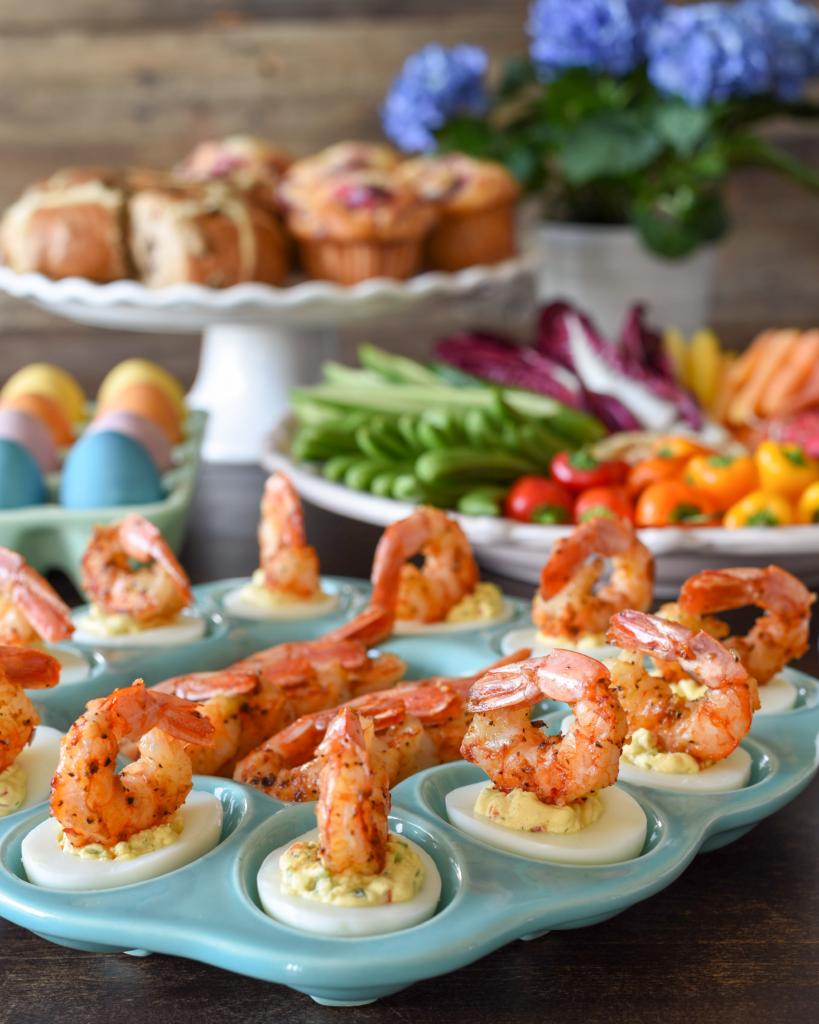 Shrimp on creamy deviled eggs presented on an egg platter.