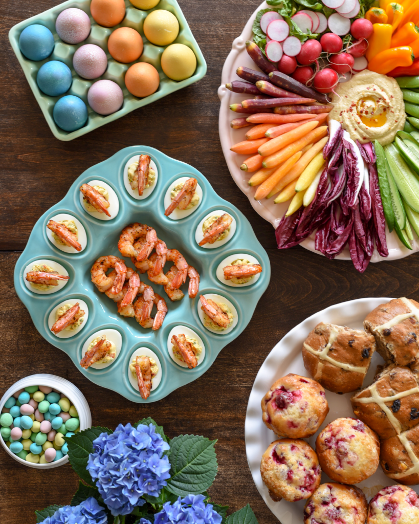 A selection of Easter food including dyed eggs, shrimp deviled eggs, hot cross buns, mini eggs and hummus and veggie platter.
