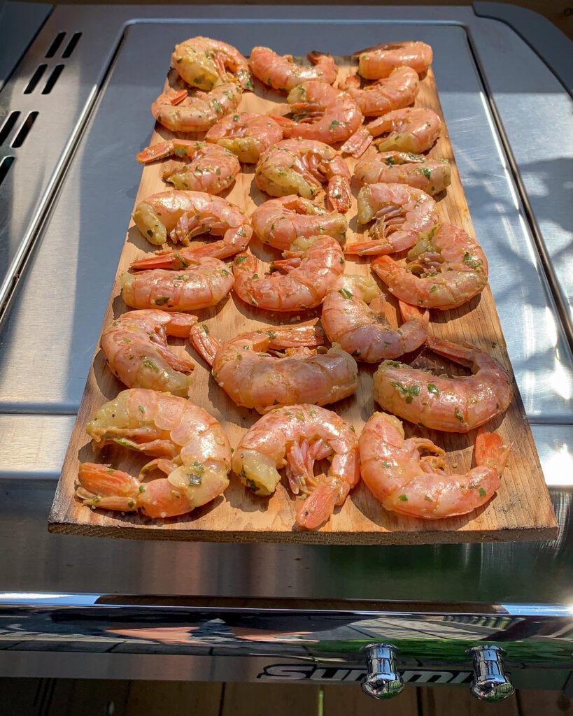 Shrimp on a cedar plank outside on barbeque.