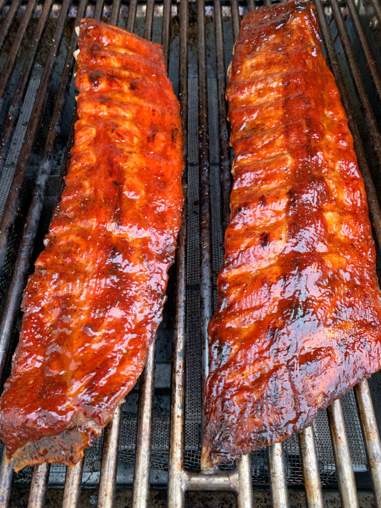 Two racks of glisening ribs on the barbeque.