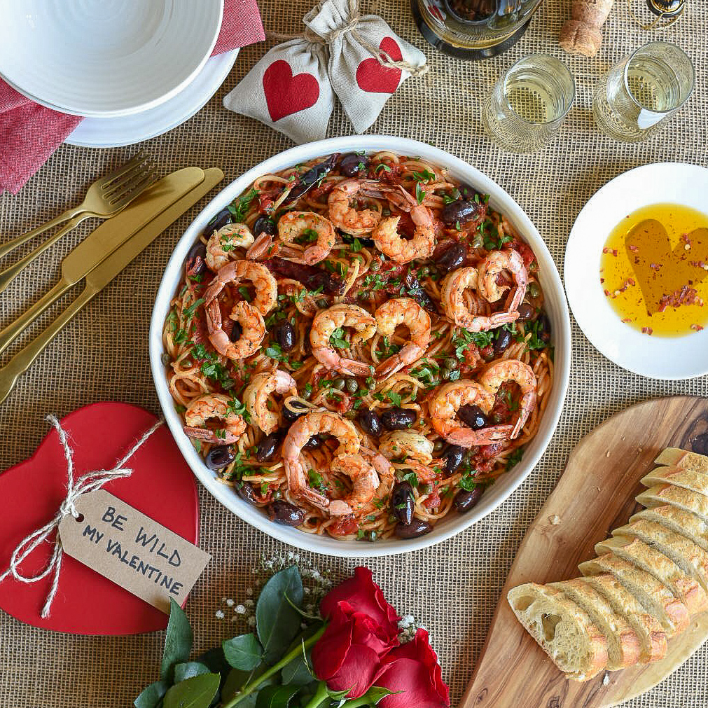 A Valentine's day meal of wild shrimp puttenesca. The shrimps placed together as hearts.