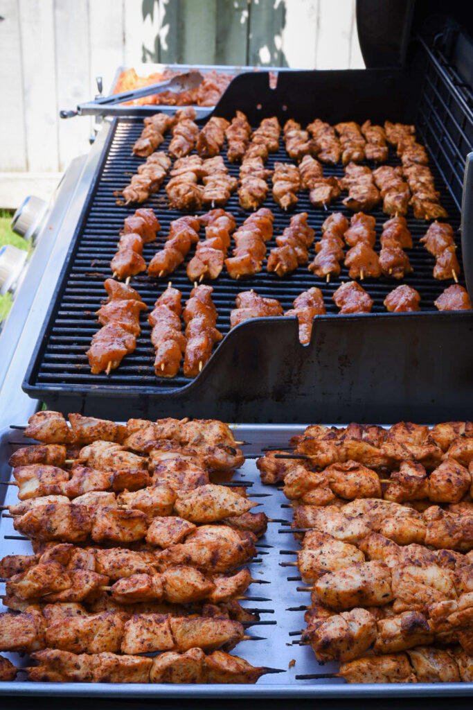 A view of a barbeque filled with souvlaki skewers grilling, plus a pile of finished skewers on the side.