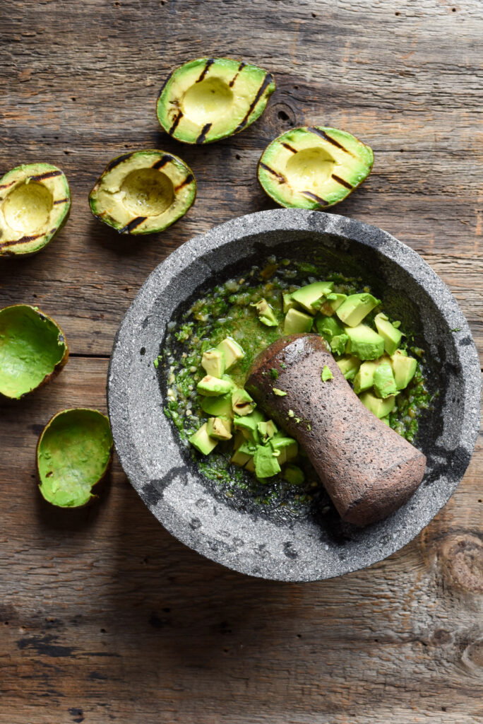 A large molcajete and tejolete (mortar and pestal) with cube of avacados ready to be smashed. Grilled avocados are ready to be scooped and added to the molcajete.
