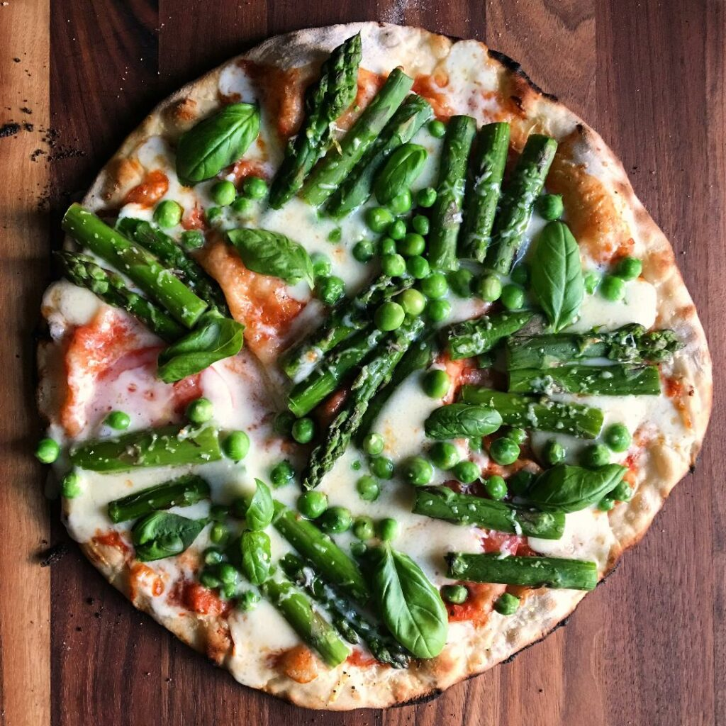 Wood oven green pizza with peas asparagus and basil.