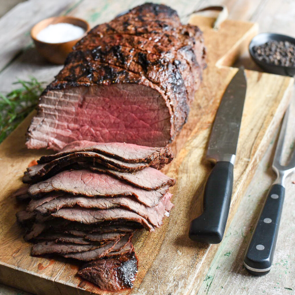 Grilled roast beef on a cutting board. Half of the beef is sliced thinly, a carving knife and fork are on the board.