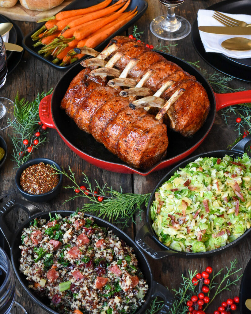 Top down view of a diner table with two racks of pork in a red skillet pan.  Plus a dish of carrots, quinoa salad, and brussels sprouts,