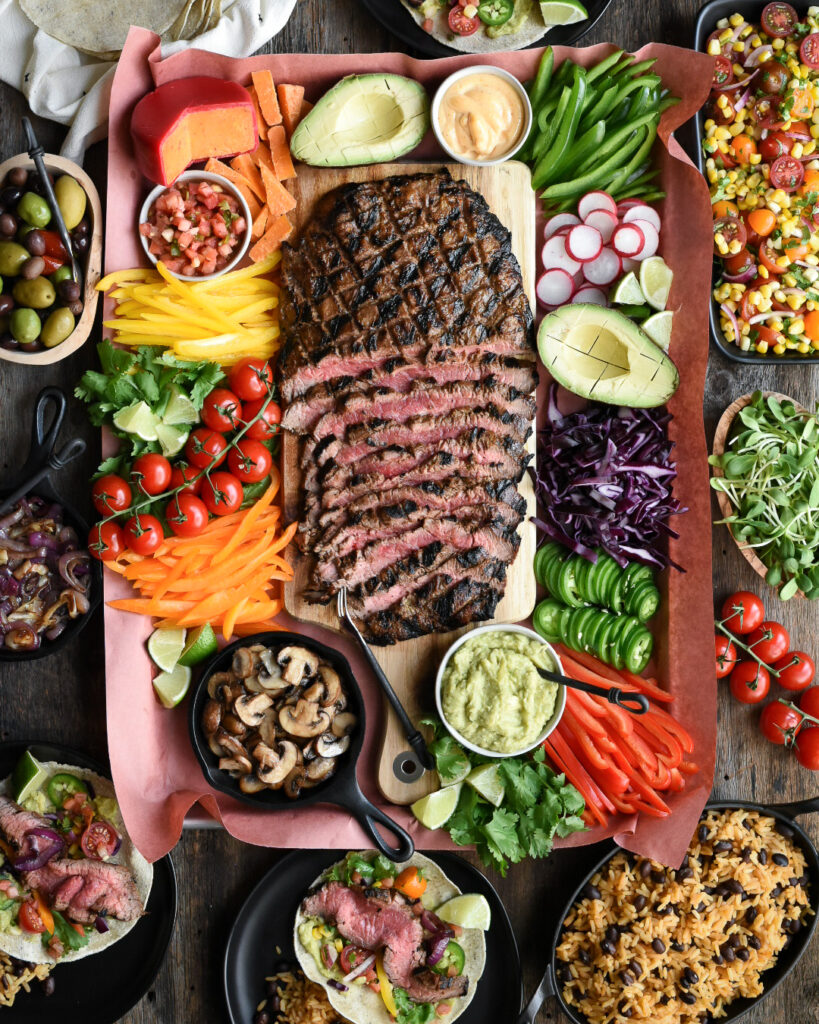 Top down view of  a flank Steak sliced with taco ingredients surrounding. Ingredients include avocado, radishes, cabbage, jalapenos, sauted mushrooms in a mini cast iron skillet, guacamole, tomatoes on vine, mixed olives, cheese wheel with red wax, corn and tomato salad, rice and beans, and two tacos filled on black plates.