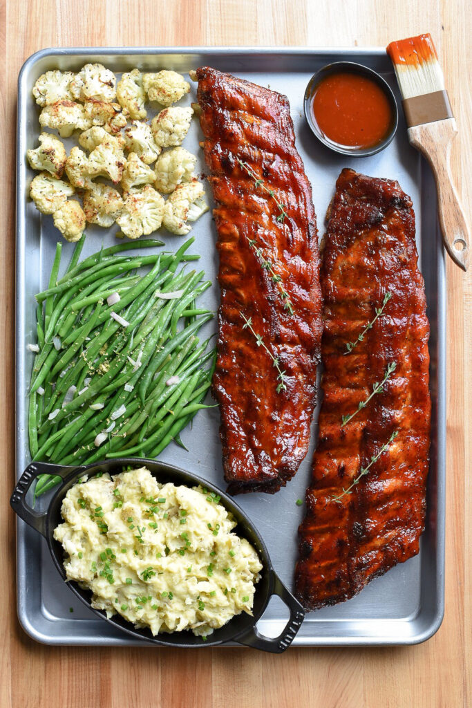 Sheet pan filled with two racks of ribs, cauliflour, green beans and mashed potatoes. Extra sauce in bowl with a brissel brush.