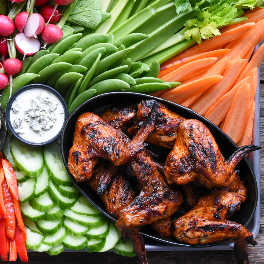 An oval bowl of grilled whole chicken wings on a platter with a veggies including celery, snap peas, radishes, cucumber, carros and two bowls of dip.