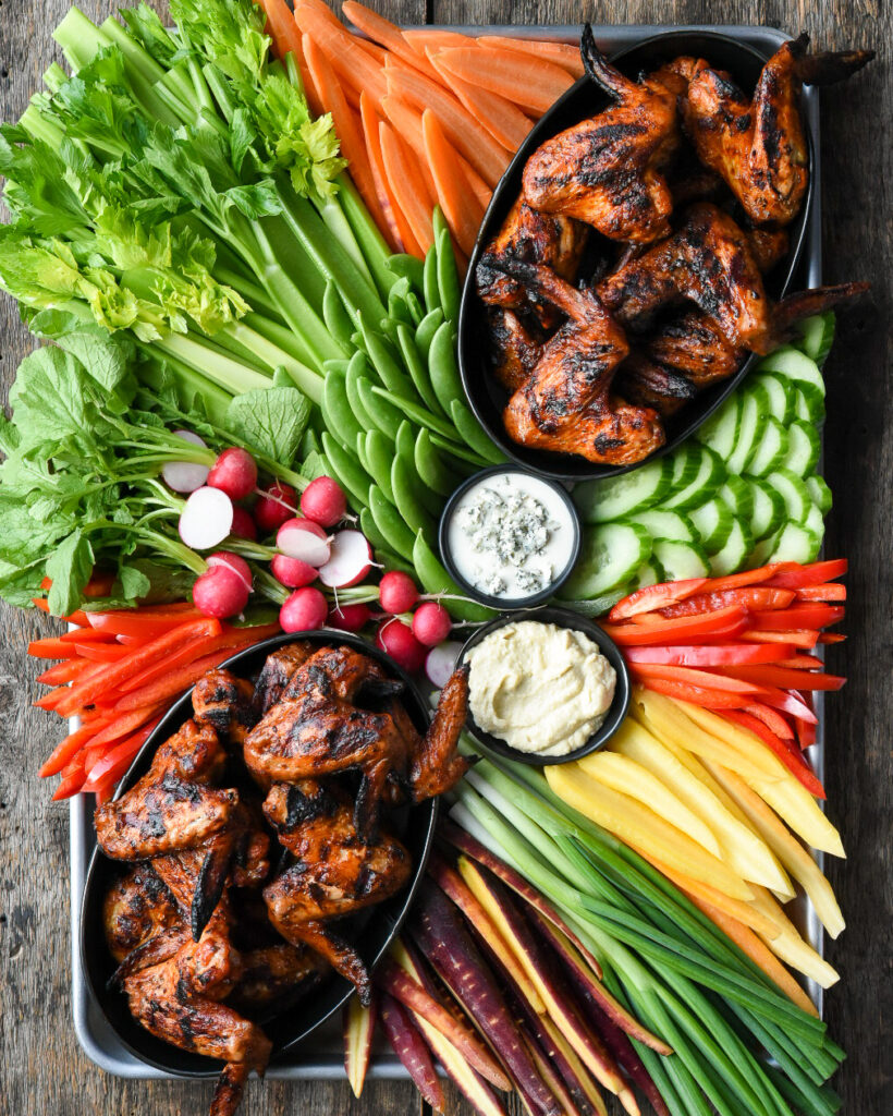 Two oval bowls of grilled whole chicken wings on a platter with a veggies including celery, snap peas, radishes, cucumber, carros and two bowls of dip.