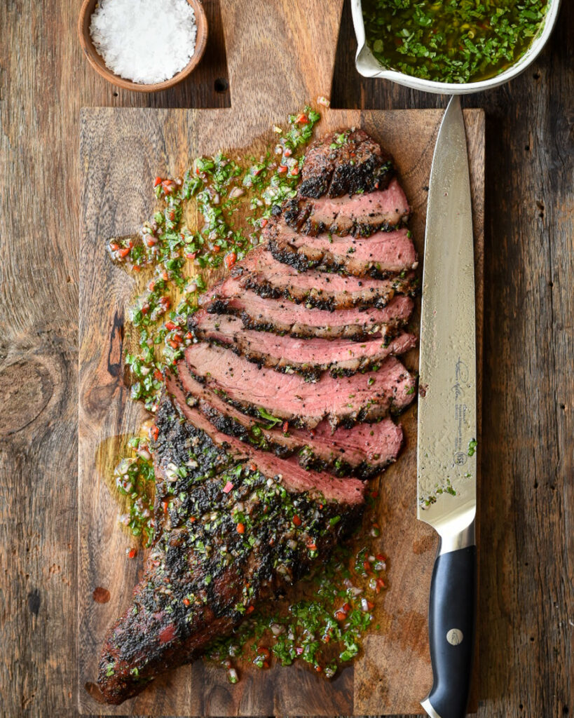 Tri-tip steak sliced on a wooden board with a large knife. Bowl of chimichurri and a bowl of salt.