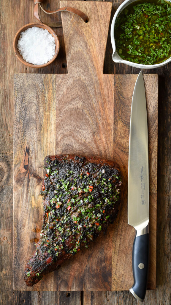Tri-tip steak on a wooden board with a large knife. Bowl of chimichurri and a bowl of salt.