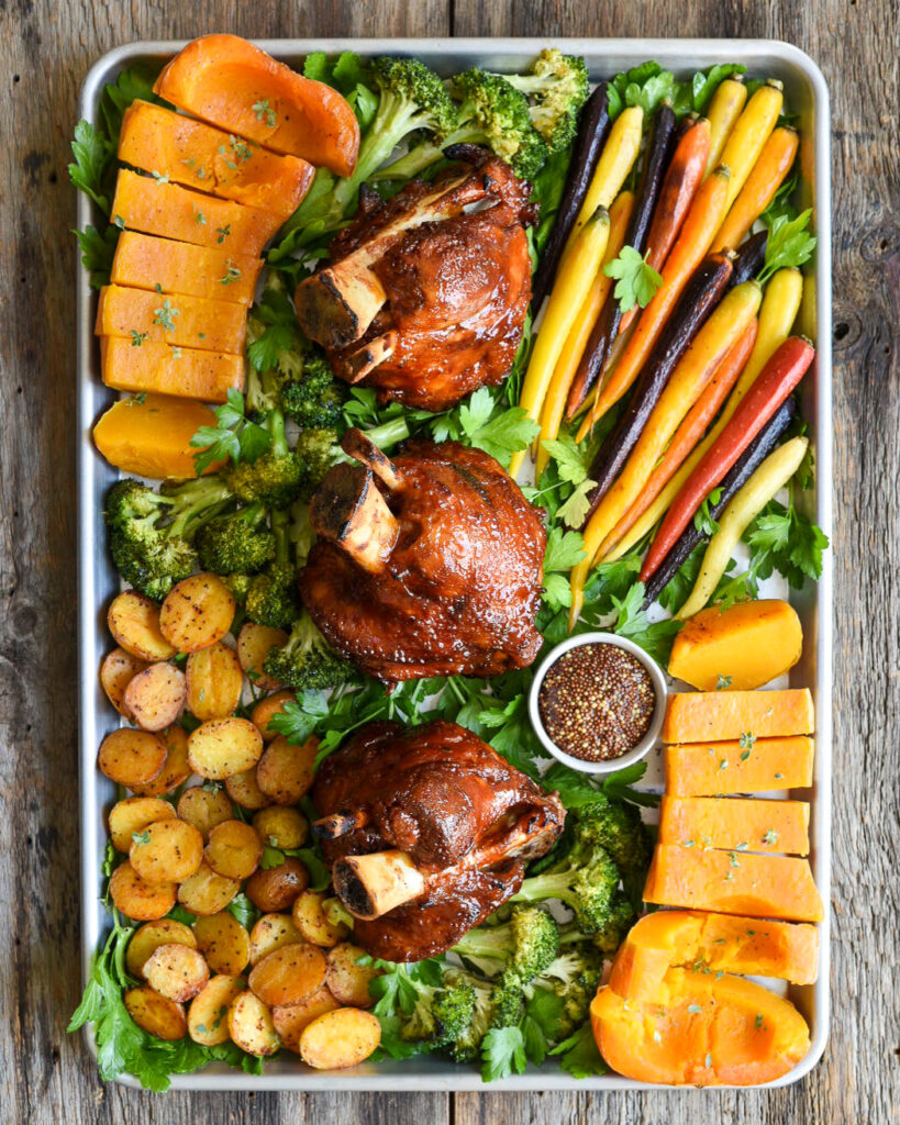 A sheet pan filled with three grilled pork hocks, roasted carrots, squash, broccoli and potates all on a bed of parsley.