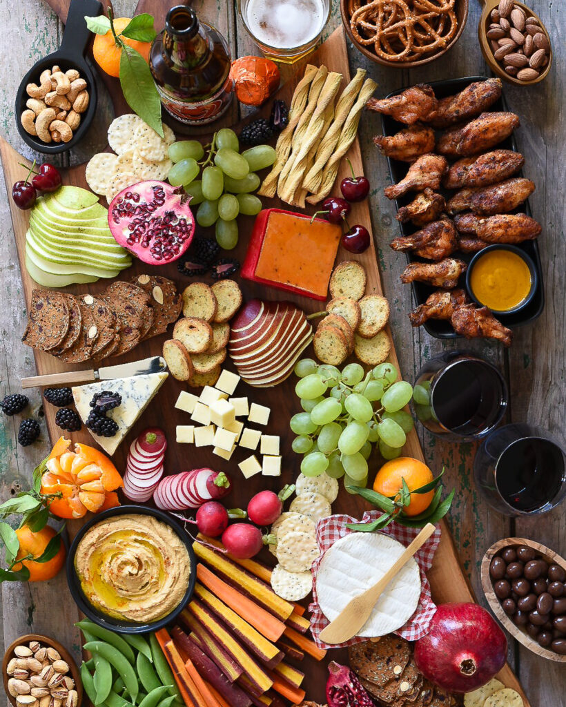A large appetizer board with chicken wings, hummus and veggies, cheese and crackers, fresh fruit, pretels, nuts, chocolate almonds, wine and beer.