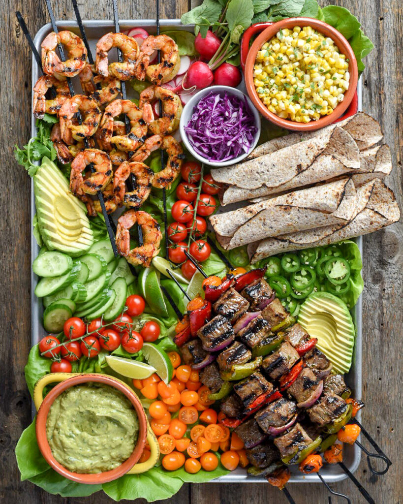 Surf and turf tortillas served on sheet pan with all the fixings.