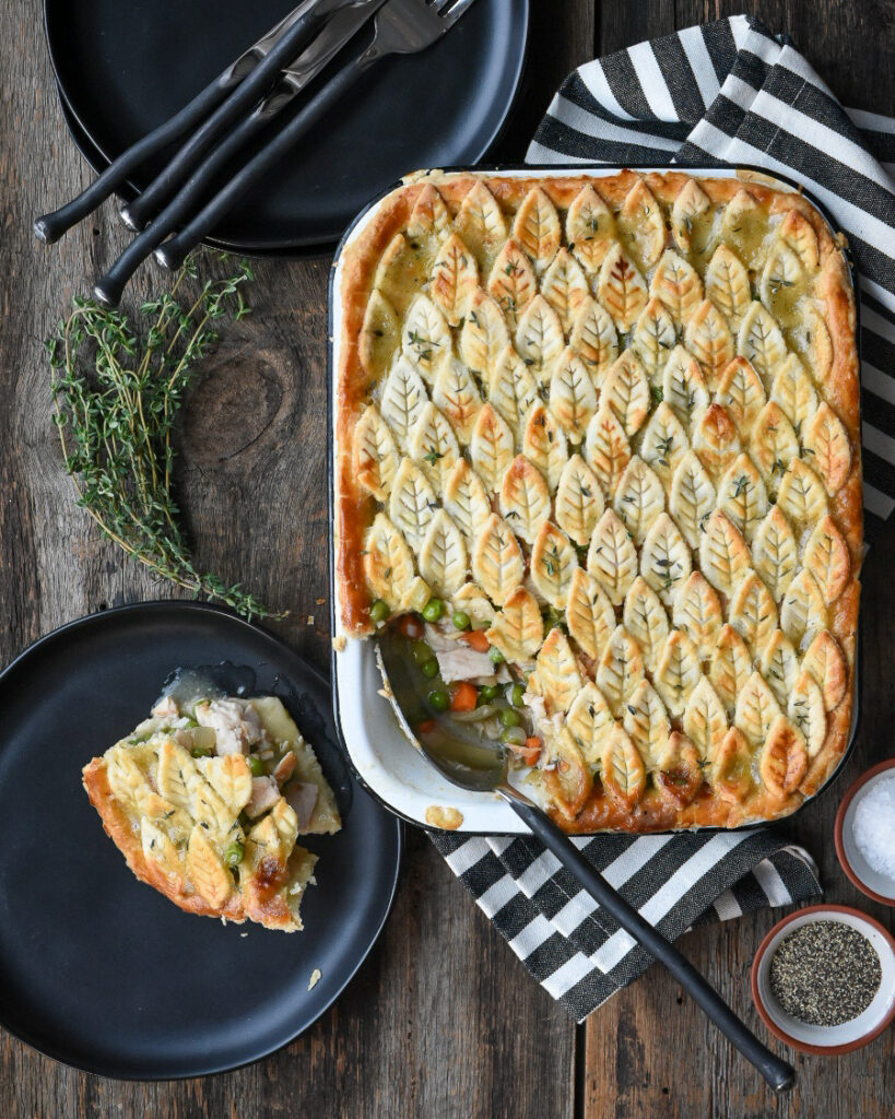 Turkey pot pie with leaf decorated crust. Black plates and striped cloth.