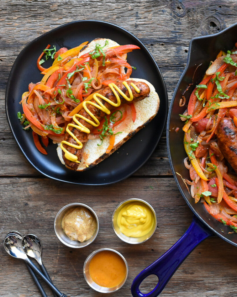 Ontario pork hot Italian sausages with peppers and onions in a blue cast iron skillet and on a bun on a black plate.  Three bowls of mustard.