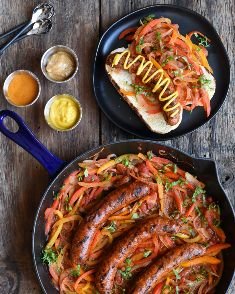 Ontario pork hot Italian sausages with peppers and onions in a blue cast iron skillet and on a bun on a black plate. Three bowls of mustard