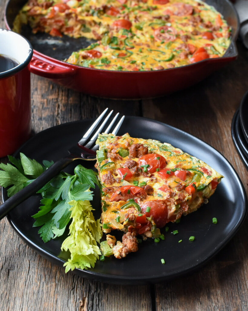 Ontario Pork Hot Italian Sausage Frittata in a red cast iron skillet and a slice on a black plate with a black fork.
