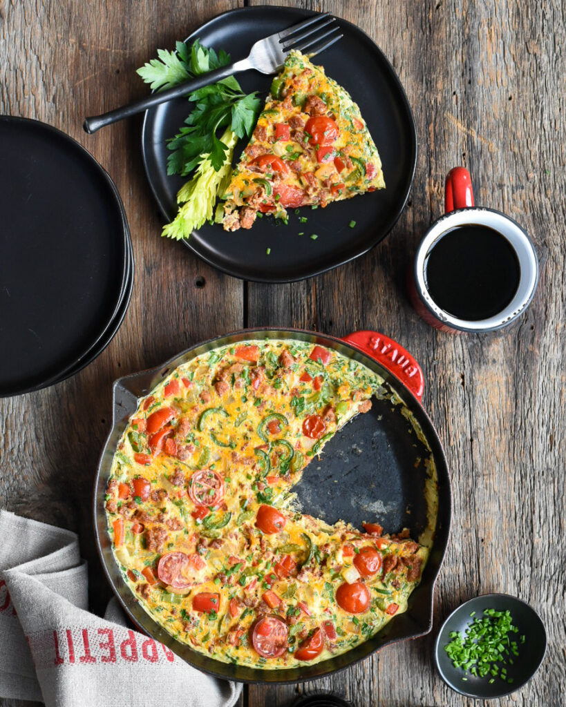 Ontario Pork Hot Italian Sausage Frittata in a red cast iron skillet and a slice on a black plate with a black fork and a red cup of black coffee.