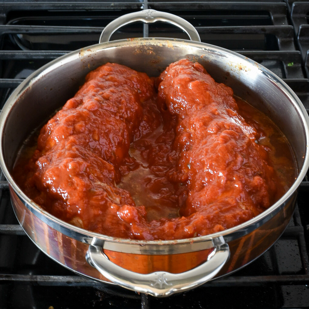 Two pork tenderloins simmering in a tomato sauce in copper pot with two handles.