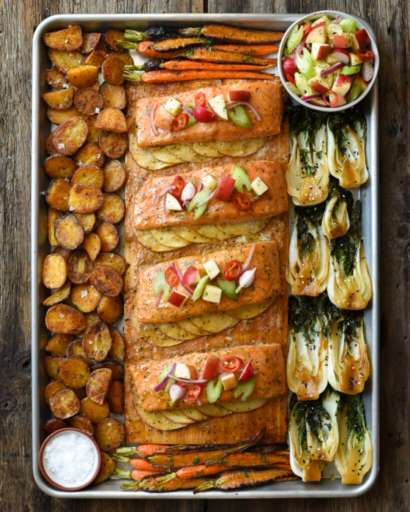 This is an image of a cedar planked salmon on slices of apples with an apple salad on top. This dish is placed in a sheet pan. Around the salmon are roasted potatoes, bok choi and heirloom carrots.