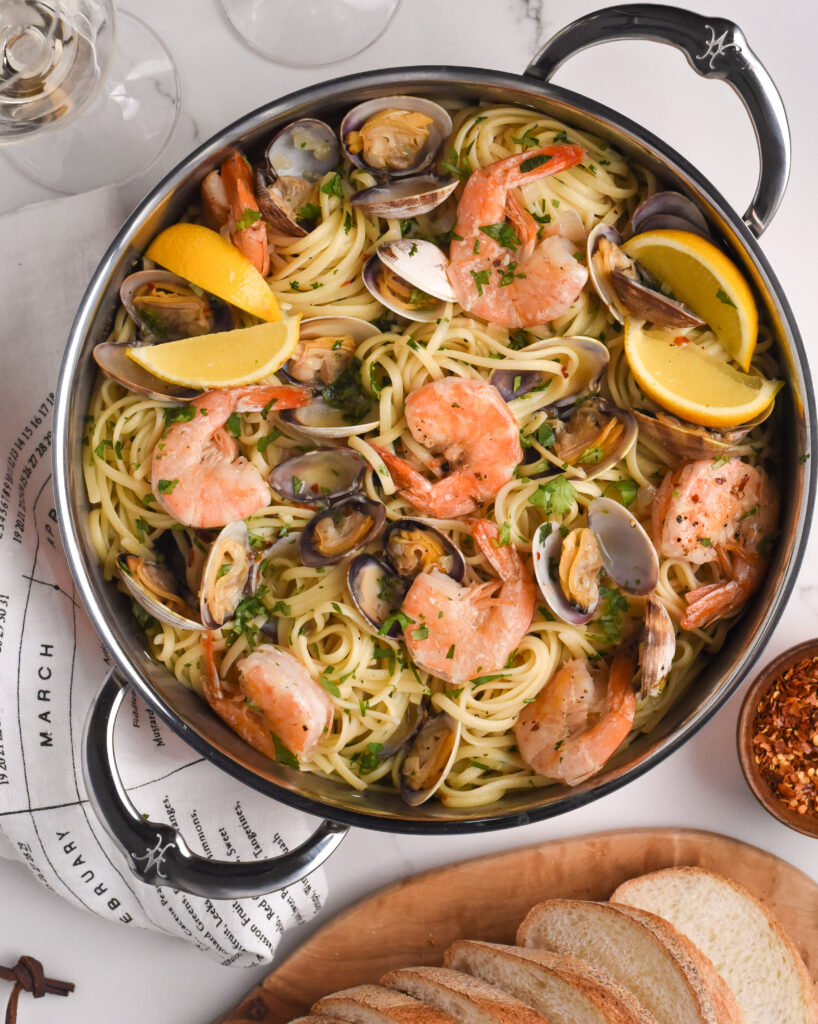 Linguine with Clams and Shrimps in a two handled pan with lemon slices.  Bread, wine and chili flakes surround the pan.