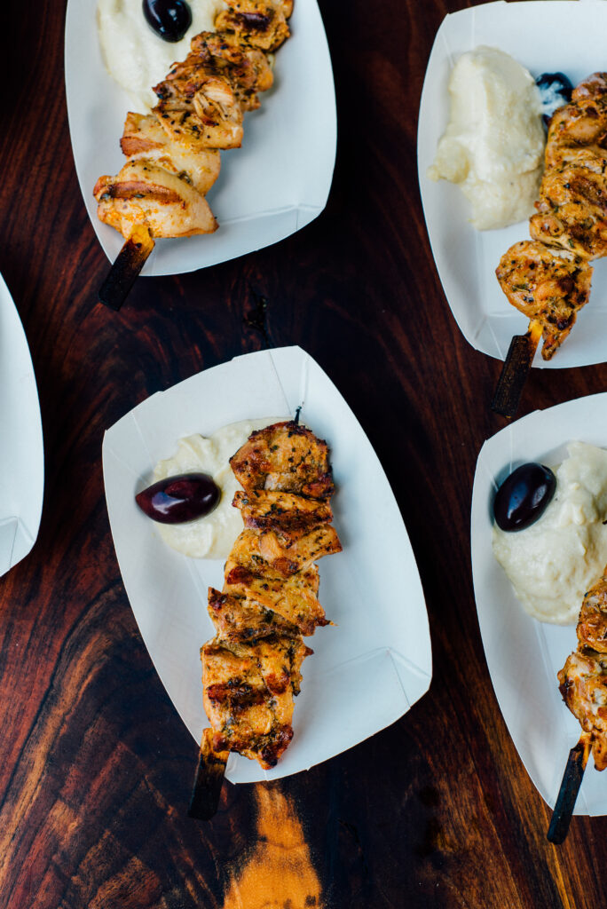 Four paper boats with a chicken skewer with hummus and an olive.