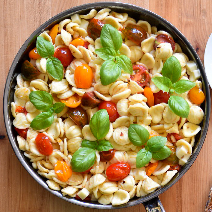 A large pan of Orecchiette with Heirloom Tomatoes, Mozzarella and basil.