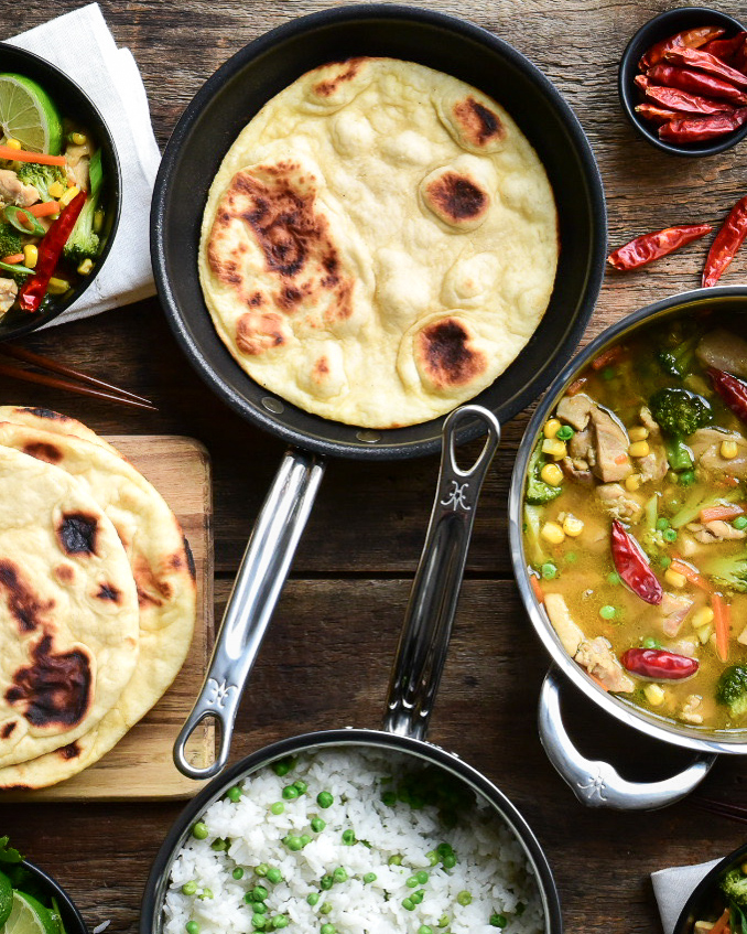 Top down image of a flatbread in a pan, a pot of Thai green curry, a pot of rice and peas and a stack of flatbread (naan).