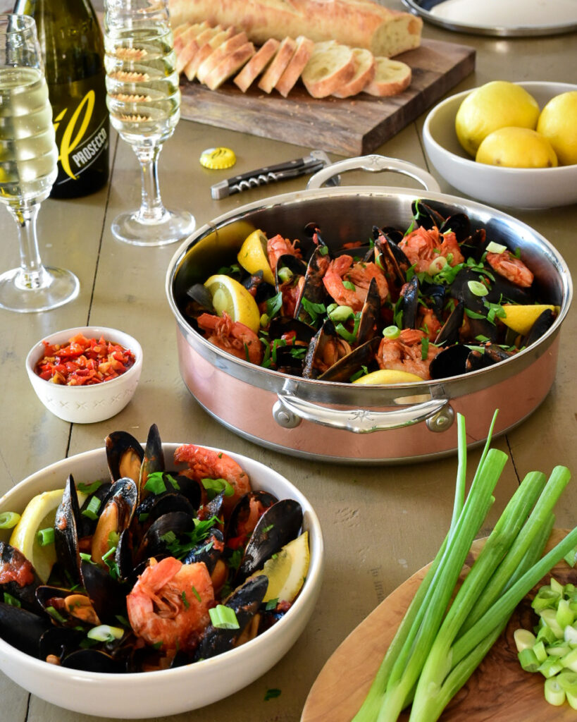 Mussels and shrimp in a Copper pan with glasses of procecco, bread, lemons and herbs surrounding it.