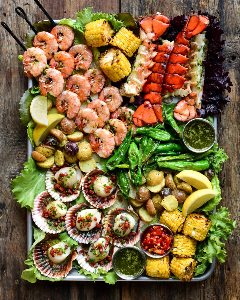 Colourful platter of grilled seafood with corn, potatoes and shishito peppers.