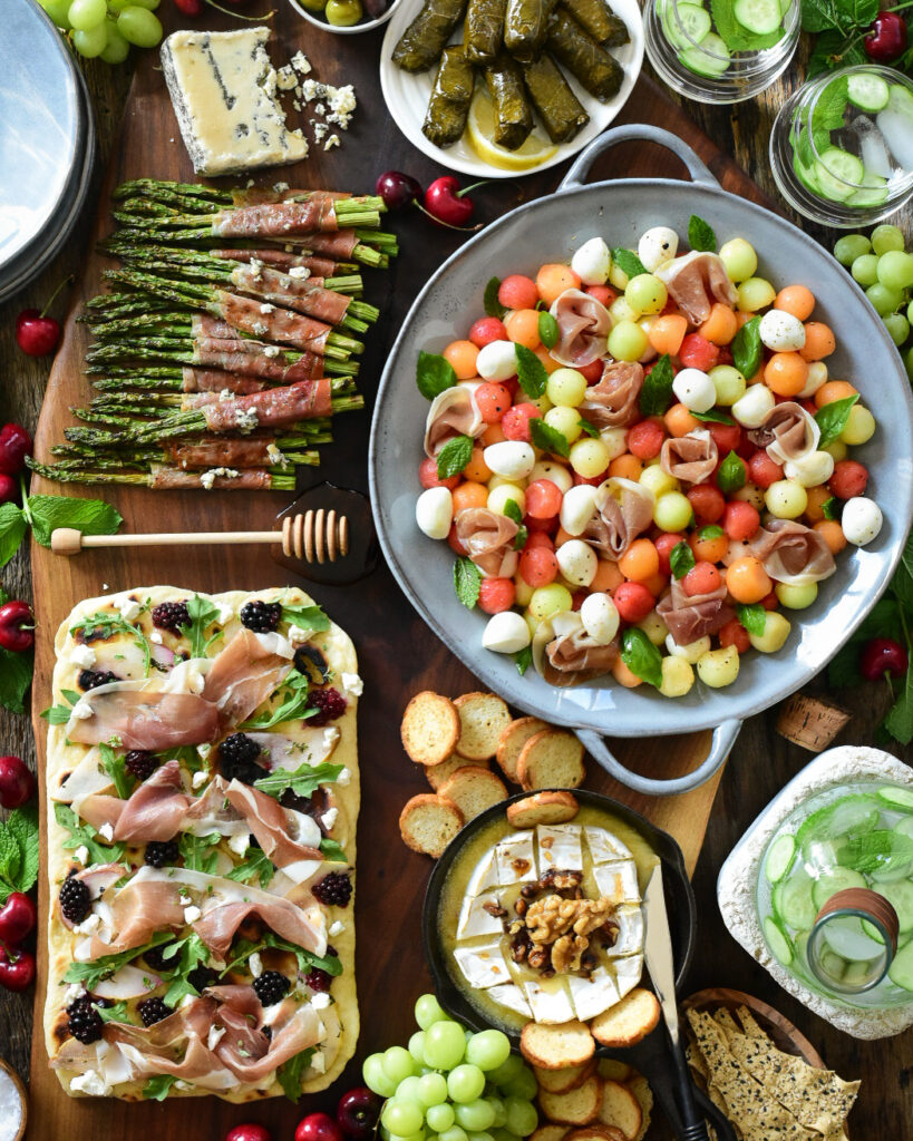 Large appetizer board with a Prosciutto and Mixed Melon Salad, Homemade Flatbread with Prosciutto, Poached Pears & Blackberries and Prosciutto Wrapped Grilled Asparagus.