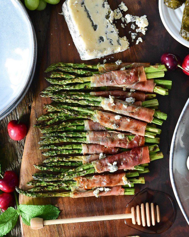 Asparagus wrapped in prosciutto in a dish ready to be grilled.