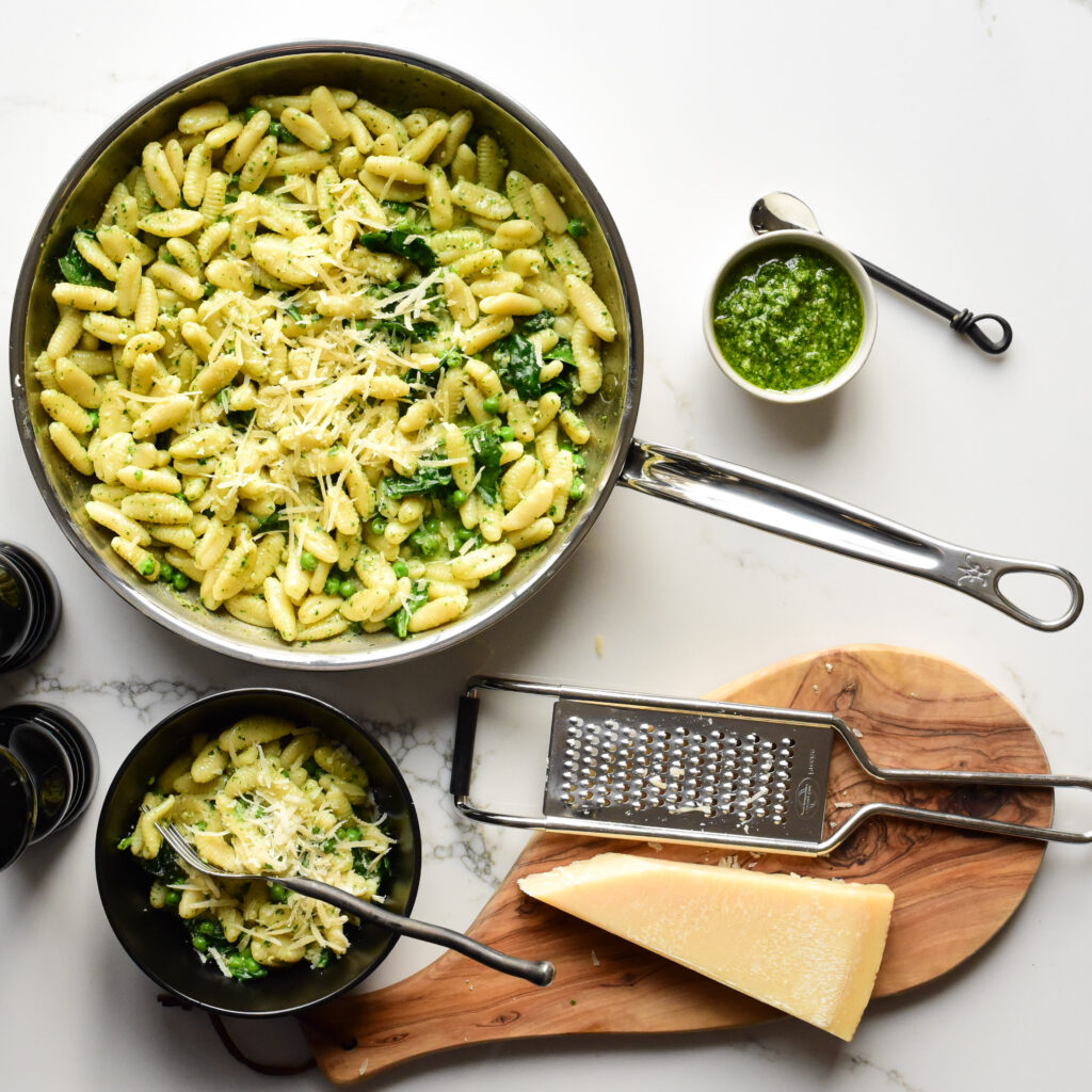 Top down view of a skillet of pasta surrounded with a bowl of pasta, pesto,  cheese and a grater