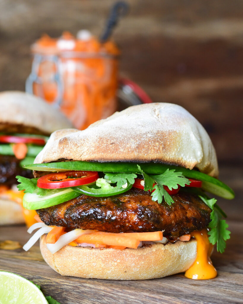 Close up image of a Bahn Mi inspired pork burger with fresh veggies and dripping sauce.