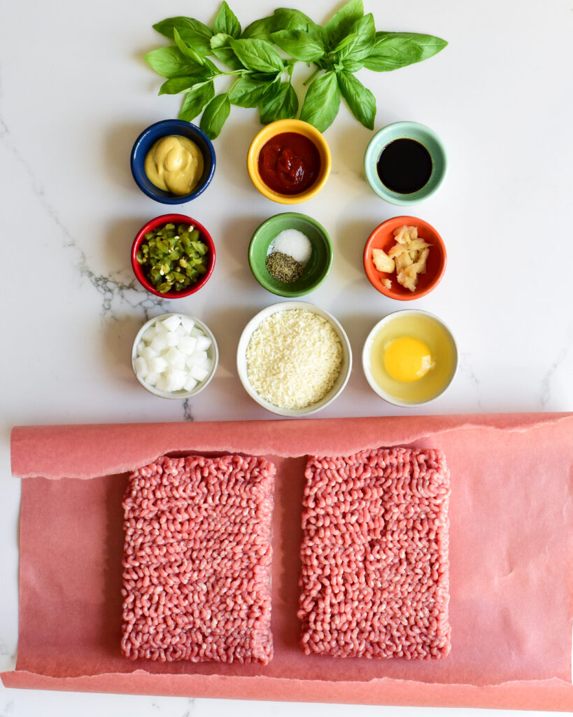 A top down view of ingredients for a Bahn Mi inspired pork burger which include nined small bowls of dry and wet ingredients and fresh ground pork.