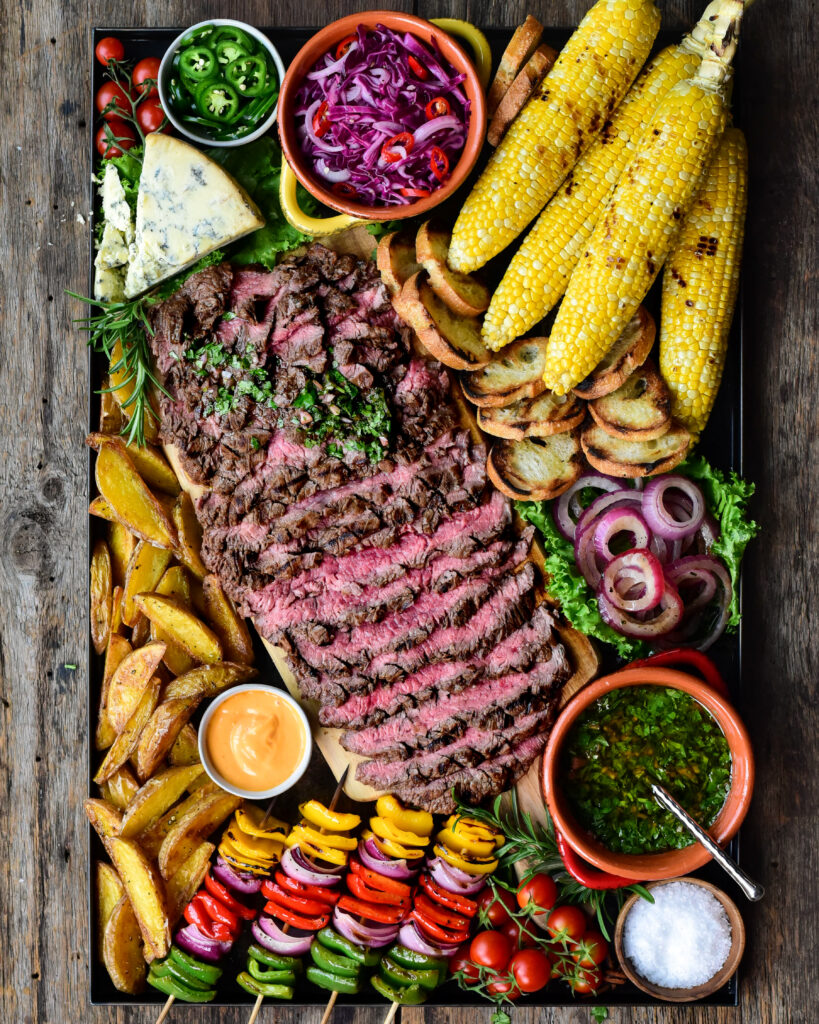Platter filled with slice flank steak beef, corn, potatoes, skewered veggies and chimichurri sauce.
