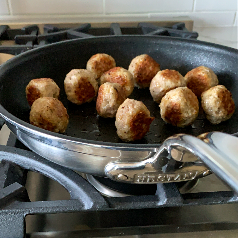 Browning turkey meatballs in a non-stick Hestan skillet.