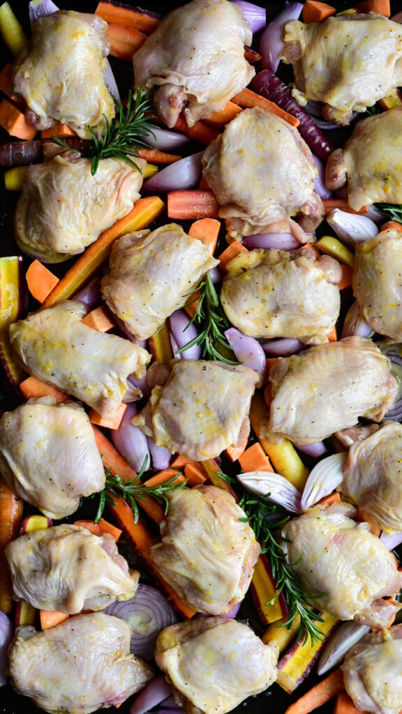 A sheet pan of veggies and chicken thighs ready to go into the oven