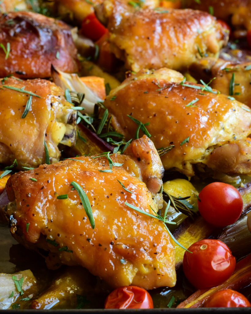 Close up photo of  a sheet pan of chicken thights with rosemary, taragon and veggies.