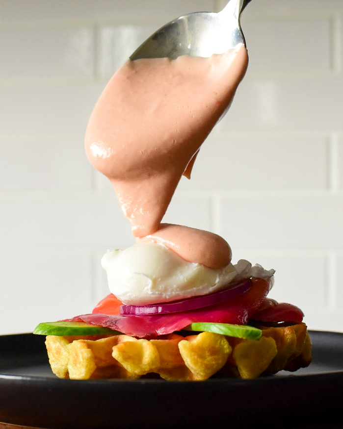 A side view image of a buttermilk waffle, layered with cucumber, beet cured salmon gravlax, red onions, a poached egg with a spoonfull of beet hollandaise sauce placed ontop.