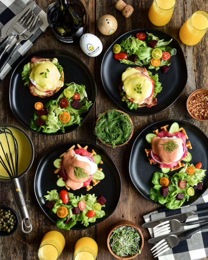 A top down view of a table with four black plates filled with salad and an eggs benedict.