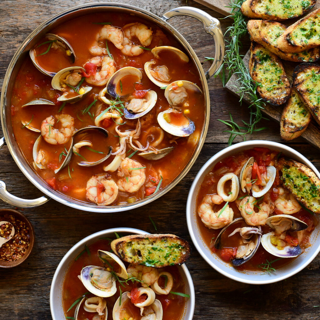 Top down images of a pot and two soup bowls filled with Cioppino (Fisherman's Stew) with clams, shrimp and squid.  Garlic and herb toast surrounding the bowls.