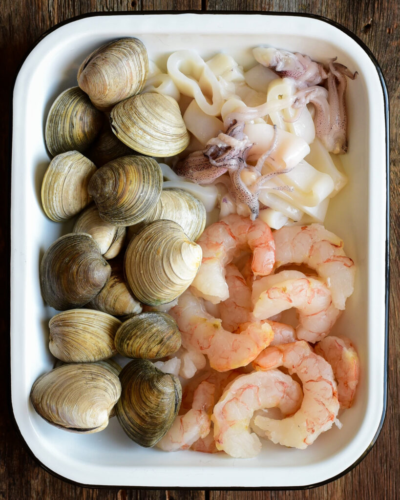 A white enamel tray with raw littleneck clams, shrimp and squid.