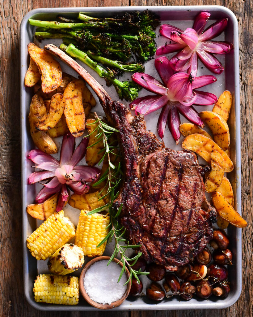 A top down image of a bone-in ribeye steak with roasted red onion flowers, potatoes and broccolini.