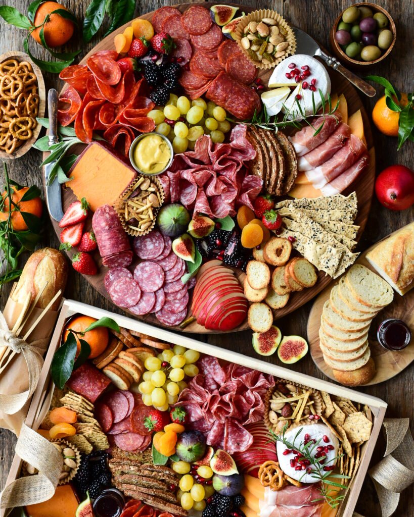 Two very colourful charcuterie boards filled with meat, fruit, nuts, and bread.