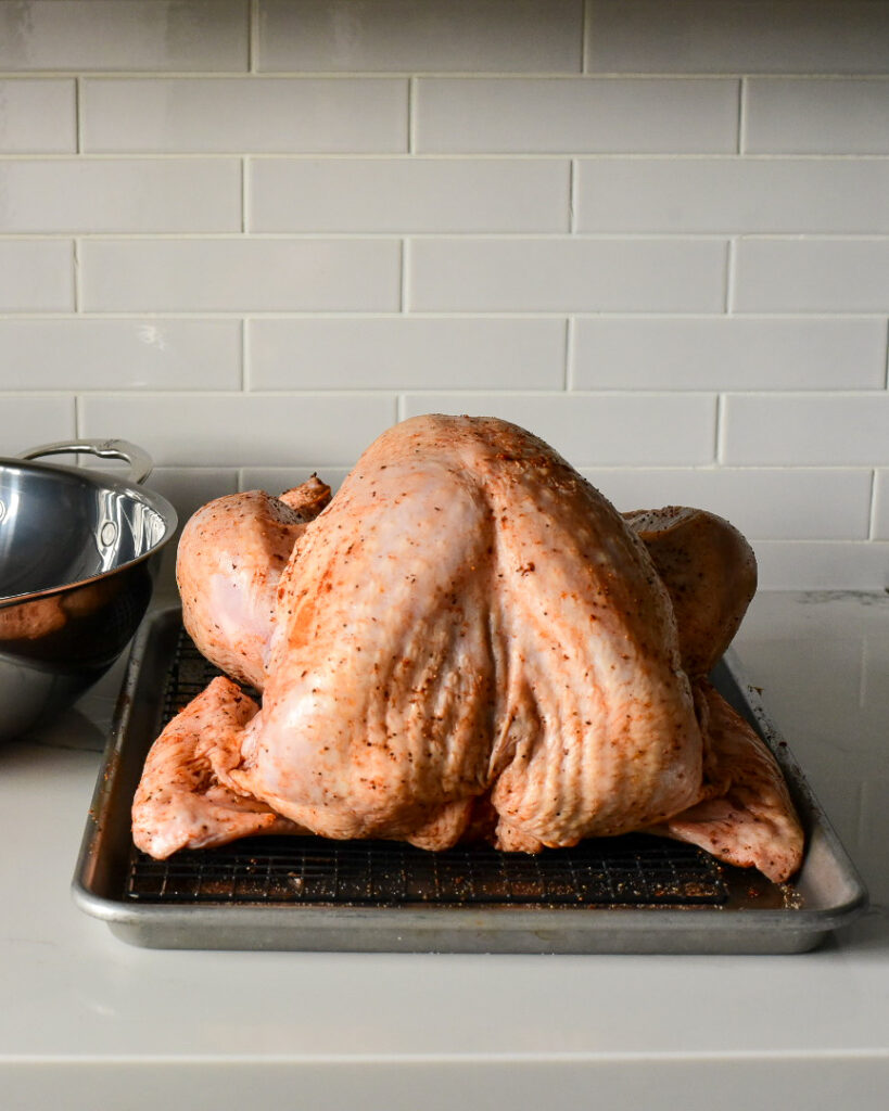 Dry rubbed turkey on a rack over a sheet pan.