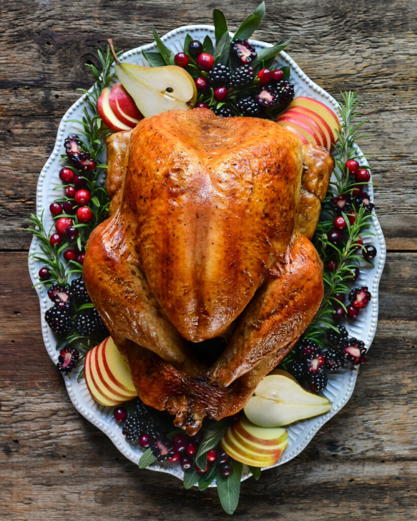 Top down image of a roasted turkey garnished with herbs and fruits on an oval scalloped platter.